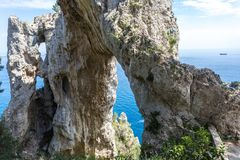 Capri Italy, island in a beautiful summer day, with faraglioni rocks and natural stone arch. Particular close up of the arches and the mediterranean sea at the Royalty Free Stock Photo