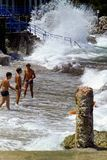 CAPRI, ITALY, JULY 1969 - Three boys defy the waves during a swell between the pebbles, the rocks and a Roman column on the beach. royalty free stock photos