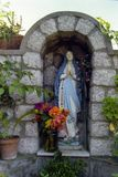 CAPRI, ITALY, 1983 - A small statue of the Madonna blesses passers-by along a street in Anacapri royalty free stock image