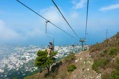 Capri lift. CAPRI, ITALY: Tourists riding up the mountain lift. Capri is a popular tourist destination and an island of Italy stock photo