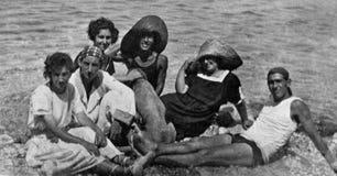 Capri, Włochy, 1932 - grupa chłopiec i dziewczyny z psem relaksujemy w Capri słońcu zdjęcie stock