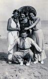 Capri, Włochy, 1933 - Trzy garbnikującej dziewczyny i ich frind żartują na plaży obrazy stock