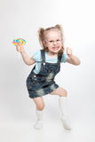 Capricious little girl with lollipop. Capricious little girl with big lollipop looking at camers royalty free stock image