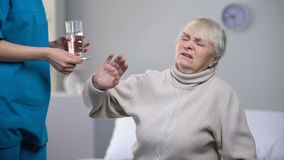 Capricious old woman rejecting medication from medical worker, treatment