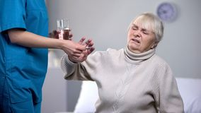 Capricious old woman rejecting medication from medical worker, treatment. Capricious old women rejecting medication from medical worker, treatment, stock photo stock photo