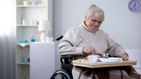 Capricious senior lady in wheelchair eating with disgust unappetizing dinner. Stock photo stock photos