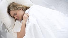 Capricious teenage girl refuses to wake up, pulling on blanket, lazy morning. Stock photo royalty free stock images