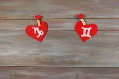 Capricorne et jumeaux signes du zodiaque et de coeur backg en bois Photos libres de droits