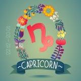 CAPRICORNIO de la muestra del zodiaco, en una guirnalda floral dulce Muestra, flores, hojas y cinta del horóscopo Foto de archivo libre de regalías