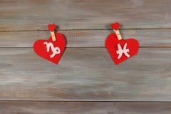 Capricornio y pescados muestras del zodiaco y del corazón Backgr de madera Foto de archivo libre de regalías