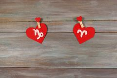Capricorno e Ariete segni dello zodiaco e del cuore backg di legno immagine stock libera da diritti
