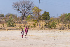 Caprivi, Namibia - August 20, 2016: Poor teenagers walking on the roadside in the rural Caprivi Strip, the most populated region i Stock Photos