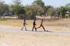 Caprivi, Namibia - August 20, 2016: Poor teenagers walking on the roadside in the rural Caprivi Strip, the most populated region i Royalty Free Stock Photo