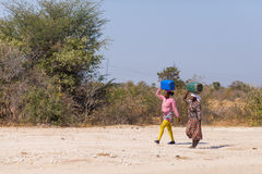Caprivi, Namibia - August 20, 2016: Poor women walking on the roadside in the rural Caprivi Strip, the most populated region in Na Royalty Free Stock Photo