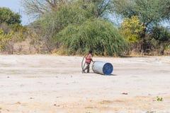 Caprivi, Namibia - 20 de agosto de 2016: Adolescente pobre que juega en el borde de la carretera en la tira rural de Caprivi, la  Imagen de archivo libre de regalías