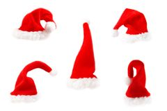Caps. Five red Santas caps on white background stock photos