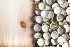 Caps of beer on a wooden board, top view. A lot of beer caps on a wooden board, top view Royalty Free Stock Images