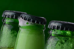 Caps on green beer bottles. Closeup of caps on three green glass bottles of beer with middle one partially opened Royalty Free Stock Images