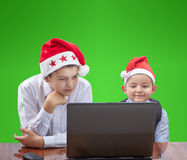 In caps of Santa Claus children with interest are looking at a laptop. In caps of Santa Claus kids with interest are looking at a laptop Royalty Free Stock Photography