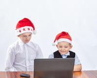 In caps of Santa Claus children look at a laptop. In caps of Santa Claus boys look at a laptop Royalty Free Stock Image