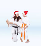 In caps of Santa Claus Mother is training the son kick leg Stock Images