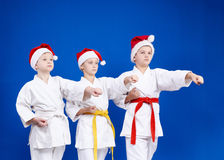 In caps of Santa Claus three athletes beat punch arm Stock Photography