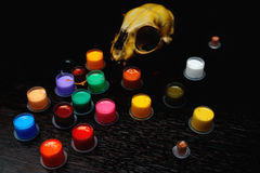 Caps for tattoo ink with colored on the background of a skull. Caps for tattoo ink with colored ink on the background of a skull. Tattoo studio. Many color ink stock photo
