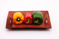 Capsicum. S on the wooden tray Royalty Free Stock Images