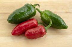 Capsicum Jalapeno annuum chili gorący pieprze, grupa zielone i czerwone owoc na drewnianym stole zdjęcia royalty free