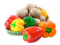 Capsicum potatoes and squash. Basket of colourful capsicum, desiree potatoes and yellow squash on a white background Royalty Free Stock Photo