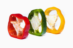 Capsicum sweet pepper sliced. Thre slices of capsicum (sweet pepper) in green red and yellow shot in studio over a white background Royalty Free Stock Photos