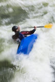 Capsize. A slow shutterspeed shot of a kayaker capsizing in very rough whitewater stock images