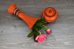 Capsize flower vase with roses. The vase is a wooden base. Water leaked out of a vase. Stock Photos