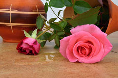 Capsize flower vase with roses. Water leaked out of a vase. Vase on ceramic tiles. Rose stock image