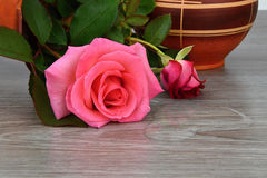 Capsize flower vase with roses. Water leaked out of a vase. The vase is a wooden base. Rose stock photos