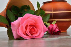 Capsize flower vase with roses. Water leaked out of a vase. Vase on a wooden base. Rose stock image