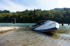 Capsized Blue Boat. A capsized boat on a river Royalty Free Stock Photography