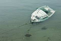 Capsized boat. A capsized boat near to the bank stock image
