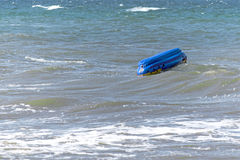Capsized inflatable boat  in the sea Stock Image