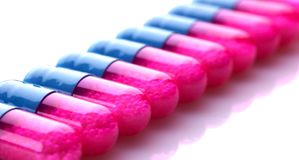 Capslules azuis e cor-de-rosa em uma fileira Imagem de Stock