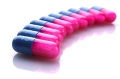 Capslules azules y rosados en una fila Imagen de archivo libre de regalías