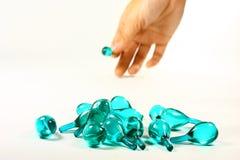 Capsula e mano blu in isolato Immagine Stock