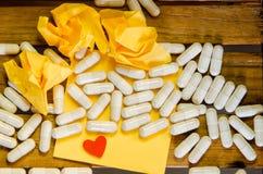 Capsule лекарство с желтым примечанием и меньшим красным сердцем стоковые изображения rf