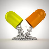From capsule. Small balls pouring from a large capsule Royalty Free Stock Images