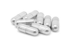 Capsule argentée de pilule sur le fond blanc Photos libres de droits