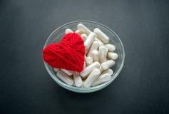 Capsule bianche del veg e cuore rosso del filo in ciotola di vetro sulla b nera immagini stock