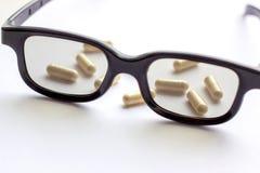 Capsule con i vetri su fondo leggero Farmacia e medicina per il concetto degli occhi fotografie stock libere da diritti