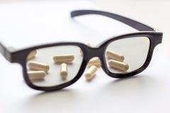 Capsule con i vetri su fondo leggero Farmacia e medicina per il concetto degli occhi fotografia stock
