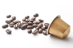 Capsule d'or de café d'expresso avec des grains de café sur W Photographie stock