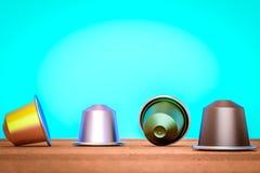 Capsule de café multicolore sur une table près des couleurs d'un vintage de mur de bleu Photos libres de droits